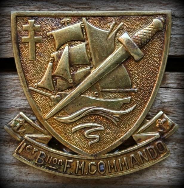"""L'insigne du 1er bataillon de fusiliers marins commandos a été dessiné par un des volontaires de l'unité, Maurice Chauvet. Evadé de France par l'Espagne, Maurice Chauvet a passé deux ans dans les prisons et les camps d'internement espagnol avant de rejoindre la Troop 8 du capitaine Trépel, un an avant le débarquement. Au début de l'année 1944, ce jeune volontaire a participé à un raid sur la côte belge. Il décrit ainsi l'insigne qu'il a imaginé : """"Sur un écu de bronze, qui est de France,portant au centre le brick de l'Aventure supporté par des vagues, surchargé d'un poignard Commando, dirigé du canton senestre du chef au canton dextre de la pointe, et décoré d'une Croix de Lorraine dans le canton dextre du chef. L'écu repose sur un ruban portant l'inscription """"1er Bllon F.M. Commando"""". Ses deux extrémités repliées montrent deux petites ancres rappelant l'origine marine de l'Unité."""" Cet insigne a été repris aujourd'hui par les commandos marine, qui le portent sur leur béret vert, à gauche."""